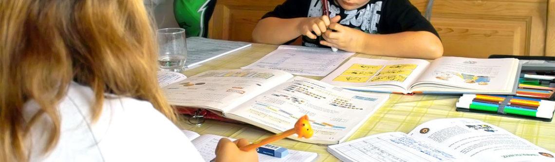 zwei Kinder am Tisch machen Hausaufgaben