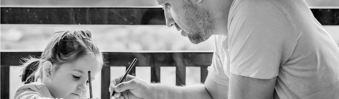 Tochter und Vater malen am Tisch